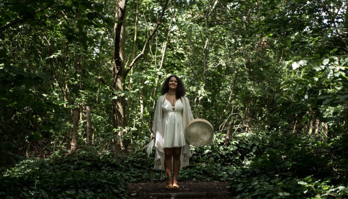 shamanic healer & coach in nature holding healing instruments and doing energy healing